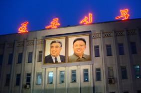 Portraits of former North Korean leaders Kim Il-Sun (left) and Kim Jong Ill (right) are lit up on the side of a building in downtown Pyongyang