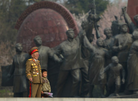 A Korean War veteran stands with a young boy at the Mansudae Grand Monuments in Pyongyang