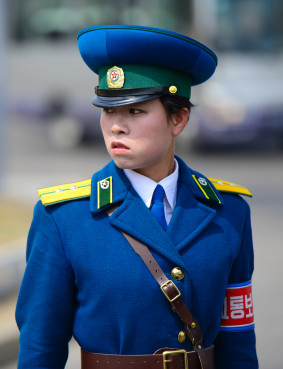 A stern faced member of the Pyongyang traffic police directs traffic in Pyongyang