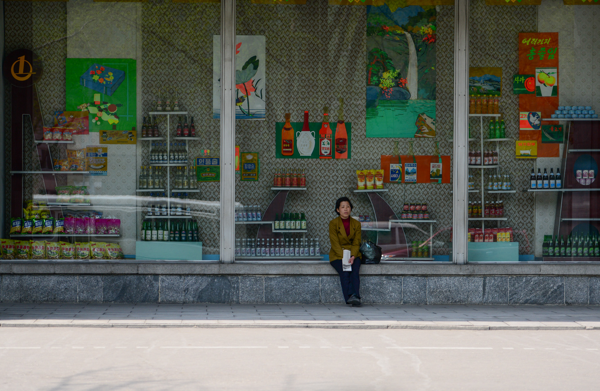 A woman rests on the window sill of a department store in Pyongyang