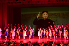 Children salute a picture of current North Korean leader Kim Jong Un during a performance at the Pyongyang Children's Palace