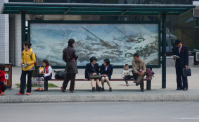 Transit commuters wait at a bus stop depicting anti-aircraft guns in Pyongyang.