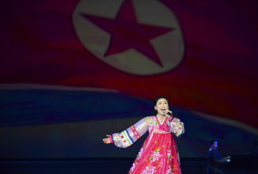 A singer performs with a North Korean flag in the background at Pyongyang Grand Theatre