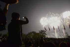 A North Korean woman photographs fireworks with her cell phone in Pyongyang.