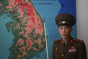 A Korean Peoples Army officer points to military positions on a map of Korea inside the DMZ.