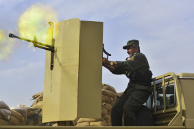 A Kurdish Peshmerga solider opens fire on an ISIS position in near Gwer, Iraq on Tuesday May 12, 2015.