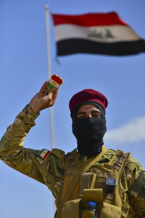 An Iraqi militia man holds up a Kurdish patch at a secret camp outside of the ISIS held city of Mosul, Iraq on May 11, 2015. The soldiers are all former residences that fled their home and are now preparing to retake their city. Gavin John