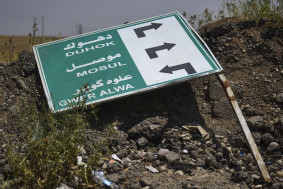 A traffic sign lies on the ground on the road to the ISIS occupied city of Mosul on May 11, 2015. Gavin John