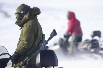 A (left) Canadian solider mounts up on a snowmobile with a (right) Canadian Ranger drives by during Operation Nunalivut near Resolute,NU on Saturday Apr 9, 2016. Operation Nunalivut featured over 200 personal from every branch of the Canadian Forces and military partners from the United States and Denmark. Gavin John/Special to PostMedia Network